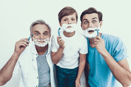 Grandfather, Father and Son Shaving Together. Spending Time Together. Father and Son. Smiling People. Parenthood Concept. Family at Home. Shaving in Bathroom. Healthcare and Hygiene Concept.