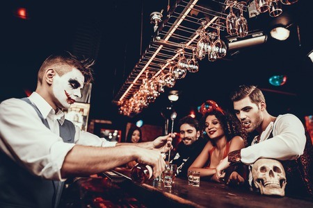 Bartender in Halloween Costume Making Cocktail. Group of Young People Wearing Costumes standing nex to Bar counter and waiting for Cocktails at Halloween Party in Nightclub. Celebration of Halloween Stock Photo