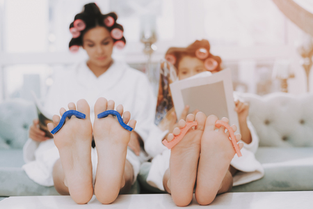 Spa Day in Beauty Salon. Little Lady with Curlers. Mother and Daughter in Spa. Consept Beauty Salon. Beautiful Face. Woman and Happy Child. Woman with Curlers. Doing Selfie. Blue Sofa in Spa Salon. Zdjęcie Seryjne