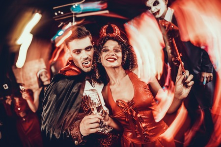 Young Happy Couple in Costumes at Halloween Party. Handsome Man and Beautiful Woman Drinking Champagne at Halloween Party in Nightclub. Friends having Fun. Celebration of Halloween Stock fotó