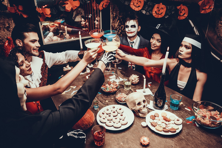 Young Smiling People in Costumes Clinking Glasses. Group of Young Happy People Wearing Costumes at Halloween Party Sitting at Table and Drinking Cocktails. Celebration of Halloween Stock Photo
