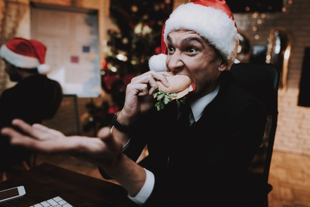 Man Watching Movie on Computer and Eating Burger. Christmas Tree in Office. Laptop on Desk. Business Concept. Man in Black Suit. Celebrating of New Year. Using Digital Device. Red Cap.