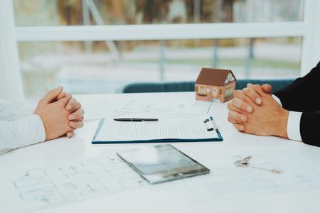 Nahansicht. Vertragsunterzeichnung Konzept. Immobilien kaufen. Helles Büro. Geschäftstreffen. Kunde und Käufer. Diskussion anbieten. Berufliche Vereinbarung. Angebot zum Hausverkauf. Unterschrift des Dokuments.