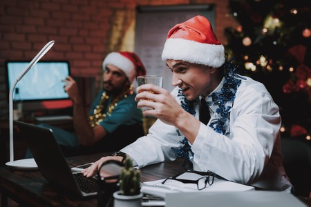 Two Smiling Doctors Celebrate New Year in Office. Man in Santa Claus Cap. Christmas Tree in Office. Computer on Desk. Man in White Coat. Drinking Alkohol. New Year Party. Celebration with Colleague. Stock Photo