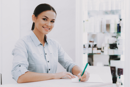 Woman Receptionist. Receptionist in Workplace. Workplace in Beauty Salon. White Interior. White Reception Desk. Beauty Consept. Smiling Salon Employee. Customer Registration. Consept Beauty Salon.