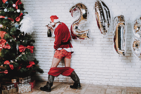 Drunk man in Santa costume standing beside Christmas Tree in Office