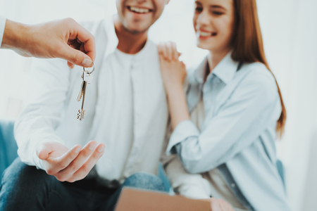 Young Couple Stare On The Key In Rieltors Hands. Bright Office. Keys In A Hand. Buying A Property. Panoramic Windows. Business Meeting. Customer And Buyer. Offer Discussion. Professional Agreement. 版權商用圖片