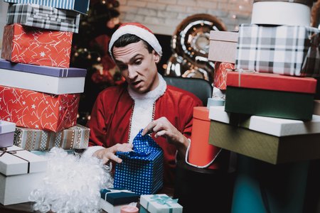 Young Man in Santa Claus Costume with Gift Boxes. New Year Eve. Christmas Tree in Office. Celebrating of New Year. Red Costume. Man in Red Cap. Pile of Boxes. Sitting Man. Suprized Man. Stock Photo