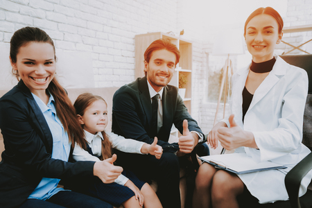 Happy Family. Psychologist in White Coat. Brown Sofa. Psychologist's Office. Write Recommendations. Notepad and Pen. Parents and Daughter. Family and Psychologist. Professional Psychologist. Reklamní fotografie