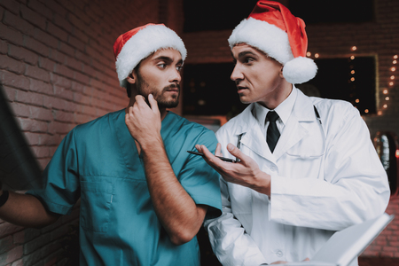 Two Doctors in Red Caps with X-ray Scan in Office. New Year Eve. Christmas Tree in Office. Computer on Desk. Man in Uniform. Celebrating of New Year. Santa Claus Cap. Medical Dispute.