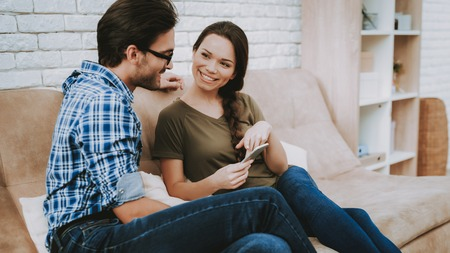 Man and Woman at Home. Woman Talking Man. Man with Glasses. Man with Tablet. Woman with Phone. Girl Shows Man Smartphone. Happy Family. Male and Female in Brown Sofa. White Pillows in Brown Sofa. Stockfoto