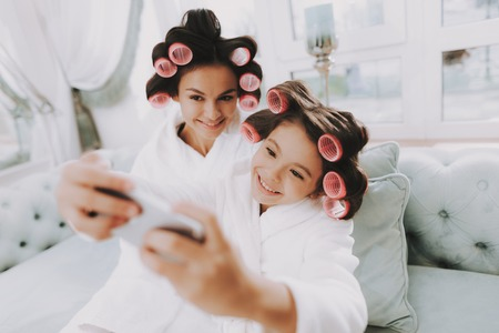 Little Lady with Curlers. Mother and Daughter in Spa. Consept Beauty Salon. Smiling Mother and Girl. Beautiful Face. Woman and Happy Child. Woman with Curlers. Doing Selfie. Blue Sofa in Spa Salon. Фото со стока
