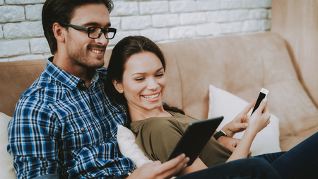 Man and Woman at Home. Woman Looks Tablet. Man with Glasses. Man with Tablet. Woman with Phone. Girl Shows Man Smartphone. Happy Family. Male and Female in Brown Sofa. White Pillows in Brown Sofa.
