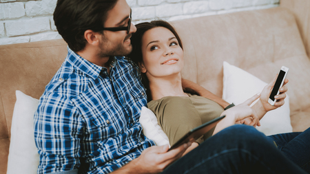 Man and Woman at Home. Man Hugs Woman at Home. Man with Glasses. Man with Tablet. Woman with Phone. Family in Room. Happy Family at Home. Male and Female in Brown Sofa. White Pillows in Brown Sofa.