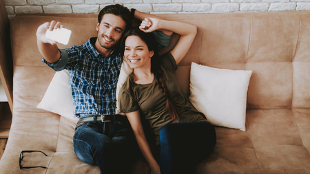 Man and Woman Make Selfie. Man and Woman Resting. Man Resting in Sofa. Woman Resting Home. Family in Room. Happy Family at Home. Male and Female in Sofa. White Pillows in Brown Sofa. Smiling Person.