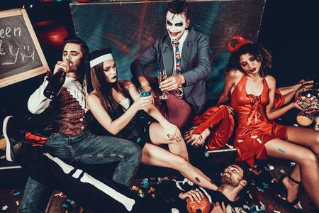 Jóvenes borrachos en trajes descansando después de la fiesta. Grupo de jóvenes amigos con disfraces descansando después de la fiesta de Halloween acostado en el piso de la discoteca y bebiendo. Concepto de vida nocturna