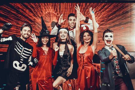 Retrato de jóvenes sonrientes en disfraces de miedo. Grupo de jóvenes amigos felices vistiendo disfraces de Halloween divirtiéndose juntos y posando para la foto de grupo en la discoteca. Celebración de Halloween