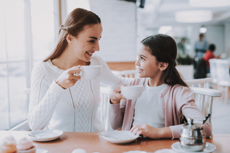 Mother and Daughter. Leisure Time. Tea Party. Smiling People. Love. Drink Tea. Have Fun. Enjoyment. Bonding. Together in Cafe. Cheerful Girls. Happy Together. Good Relationship. Happy Holidays.