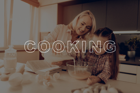 Milk. Whipped Eggs. Book with Recipes. HomeMade. Dough. Grandmother. Little Girl. Glass Bowl. Whisk. Smile. Have Fan. Thanksgiving Day. Happy Family. Kitchen. Together at Home. Celebrating Holiday.