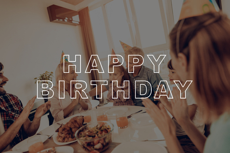 Holiday Cap. Congratulate. Cheerful Family. Holiday. Happy Birthday. Woman. Middle-Aged Woman. Celebrating. Smiling. Laughing. Together at Home. Dinner Table. Happy Family. Have Fan. Delicious Food.