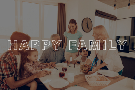 Happy Family. Salad. Holiday. Thanksgiving Day. Cups of Tea. Big Family. Dinner Table. Woman. Plate. Blue Shirt. Traditional Dinner. Have Fan. Together at Home. Celebrating Holiday. Delicious Food.