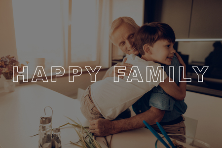 Countertop. Hugs Grandson. Sunlight. Happy Family. Dinner. Boy. Together at Home. Father. Thanksgiving Day. Have Fan. New Technology. Celebrating Holiday. Kitchen. Traditional Dinner.