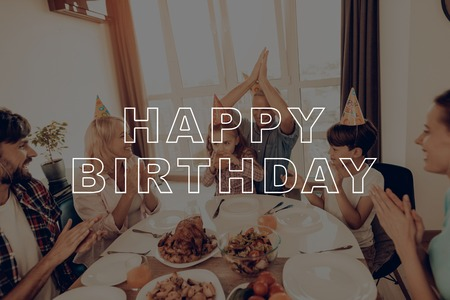 Happy Birthday. Woman. Boy. Middle-Aged Woman. Holiday Cap. Celebrating Birthday. Cheerful Family. Smiling. Laughing. Holiday. Together at Home. Dinner Table. Happy Family. Have Fan. Delicious Food. Imagens