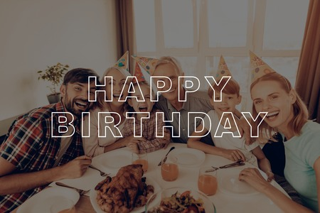 Happy Family. Girl. Laughing. Grandfather's Lap. Holiday Cap. Congratulate. Cheerful. Holiday. Happy Birthday. Woman. Celebrating. Smiling. Together at Home. Dinner Table. Have Fan. Delicious Food. Archivio Fotografico