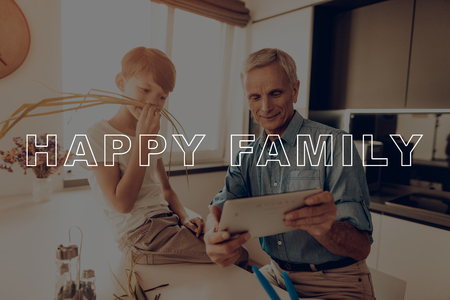Mustache from Green. Tablet. Countertop. Sunlight. Happy Family. Dinner. Boy. Together at Home. Father. Thanksgiving Day. Have Fan. New Technology. Celebrating Holiday. Kitchen. Traditional Dinner. Imagens