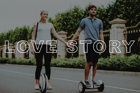 Romantic Relationships. Pair. Riding. Gyroboard. Monocle. Country Park. Happy. Fought for Hands. Love Story. Happy Together. Park. Relaxation. Smiling People. Have Fun. Young People. Stock Photo