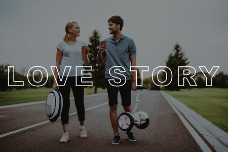 Hold Coffee. Couple. Gyroboard. Monocle. Romantic Relationships. Young People. Smiling People. Love Story. Hold Hands. Arms Apart. Riding. Country Park. Happy Together. Park. Relaxation. Have Fun.