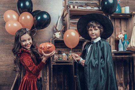 Adorable Little Children in Halloween Costumes. Cute Kids wearing Scary Halloween Costumes Standing next to Wooden Shelves with Jars full of Candys. Cute Girl and Boy Celebrating Halloween