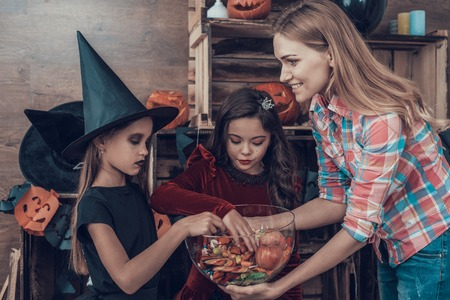Woman gives Candys to Kids in Halloween Costumes. Happy Halloween Party with Children Trick or Treating. Young Adorable Girls having Fun and getting Sweets. Celebration of Halloween