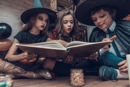 Little Children in Halloween Costumes Reading Book. Cute Smiling Kids wearing Scary Halloween Costumes Sitting on Floor next to Jars full of Candys and Candles. Celebration of Halloween