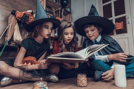 Libro de lectura de niños pequeños en disfraces de Halloween. Lindos niños sonrientes con disfraces de Halloween de miedo sentados en el suelo junto a frascos llenos de caramelos y velas. Celebración de Halloween Foto de archivo