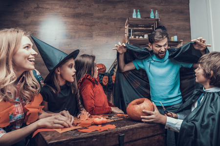 Family having Fun Making Halloween Decorations. Adorable Little Children and Young Parents in Costumes Sitting at Table and Cutting Colorful Pieces of Paper with Scissors. Celebration of Halloween