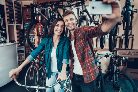 Young Guy and Girl Make Selfie at Bicycle Store.