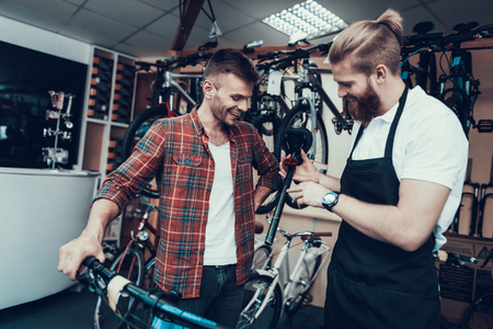 Guy and Repairman Fixes Bicycle in Sport Store. Banco de Imagens