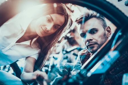 Closeup of Woman and Man look at Bike Wheel.