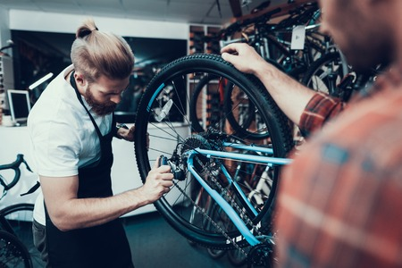 Professional Bike Repairman Fix Cycle in Workshop. Portrait of Young Caucasian Man Wearing Apron Examines Modern Cycle Transmission System Holds Hex Wrench. Bike Maintenance and Sport Shop Concept