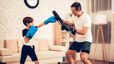 Boy Boxer. Father and Son do Spotting. Sport at Home. Warm Up in Quarter.
