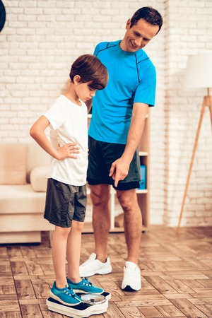 Boy Standing on Scales. Father and Son do Spotting. Sport at Home. 写真素材