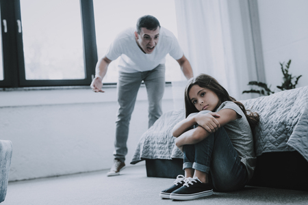 Man Screams at Sad Girl who Sitting on Floor. Stock Photo