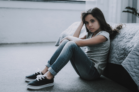 Frowning Little Girl sit on Floor in Bedroom. Stock Photo