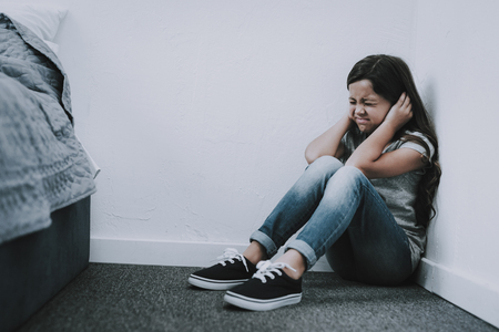 Crying Girl Sits on Floor Closes Ears and Eyes. Stock Photo