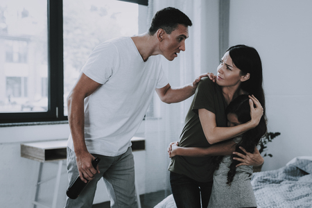 Father Screams at Wife and Daughter in Room. Stock Photo