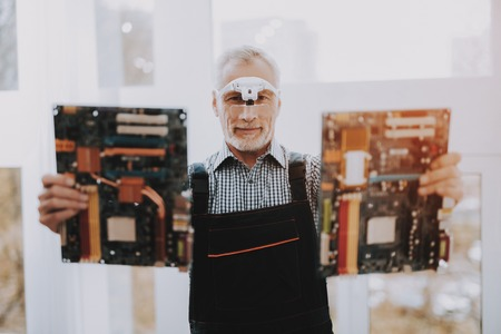 Repairman of the Computer Service is Holding Two Motherboards.
