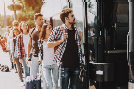 Group of Young People Boarding on Travel Bus. Happy Travelers Standing in Queue Holding Luggage Waiting their turn to Enter Bus. Traveling, Tourism and People Concept. Summer Vacation Stockfoto