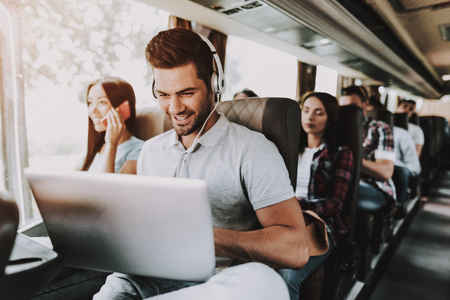Lächelnder Mann in Kopfhörern mit Laptop im Tourbus. Junger gutaussehender Mann sitzt auf dem Beifahrersitz des Touristenbusses und tippt auf Laptop. Reise- und Tourismuskonzept. Glückliche Reisende auf Reise