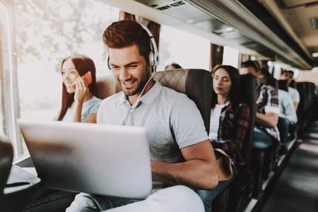 Uomo sorridente in cuffie utilizzando laptop in Tour Bus. Giovane uomo bello seduto sul sedile del passeggero del bus turistico e digitando sul computer portatile. Concetto di viaggio e turismo. Viaggiatori felici in viaggio